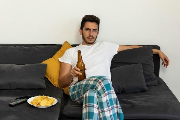 Młody mężczyzna siedzi w domu na kanapie i ogląda telewizję.