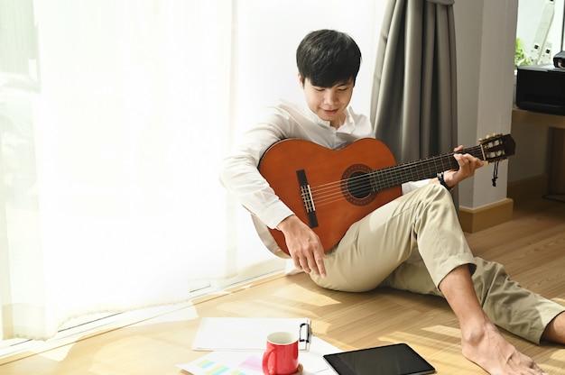 Młody mężczyzna siedzi w domu obok okna i gra na gitarze akustycznej w domu.