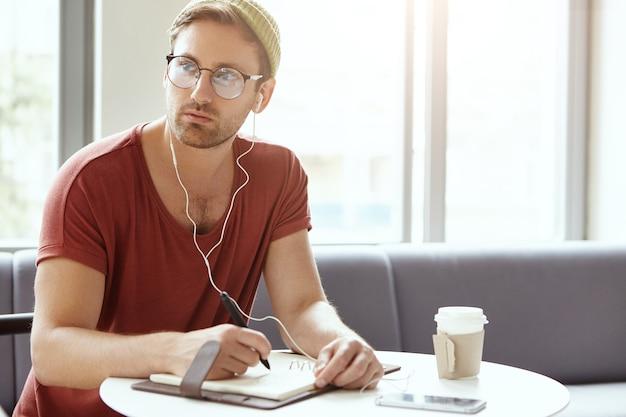 Młody mężczyzna siedzi w kawiarni, słuchając muzyki