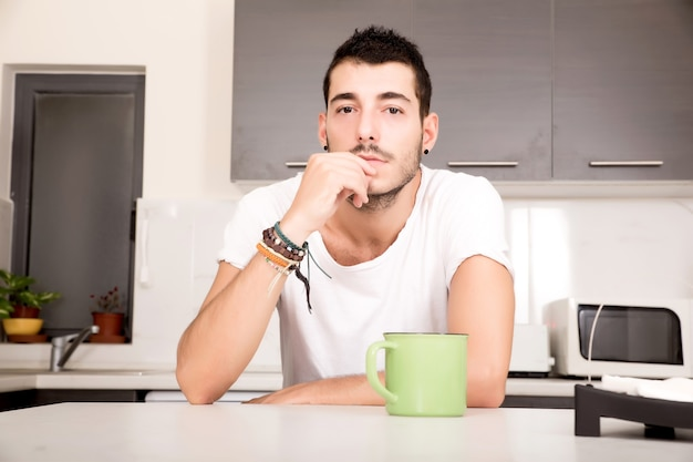 Młody mężczyzna siedzi w kuchni i pije kawę.