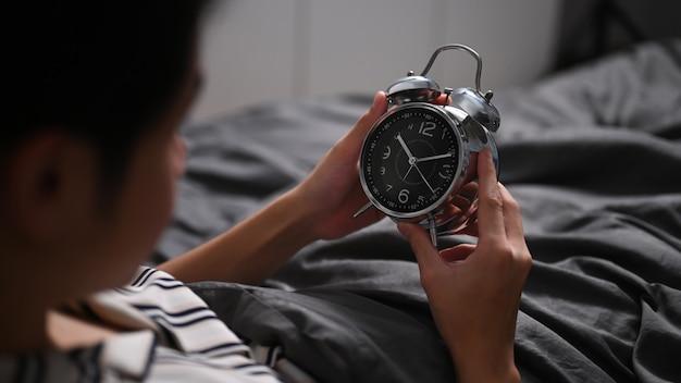 Młody mężczyzna siedzi w łóżku i wyłącza budzik.