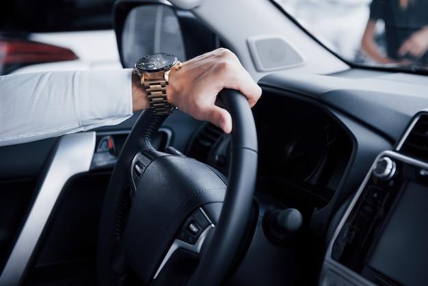 Młody mężczyzna siedzi w nowo kupionym samochodzie, trzymając się za ręce steru.
