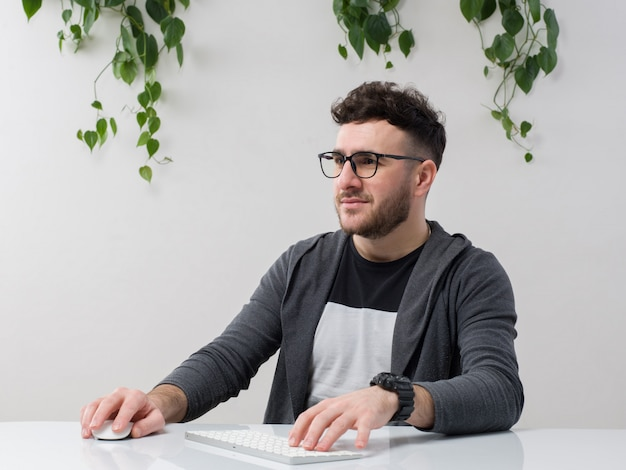 Młody mężczyzna siedzi w okularach zegarki szara kurtka pracuje na komputerze wraz z rośliną na białym tle