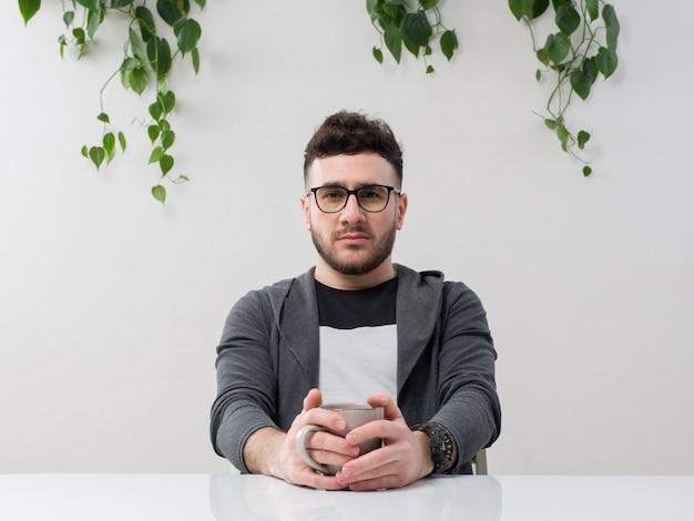 Młody mężczyzna siedzi w okularach zegarki szara kurtka wraz z rośliną na białym tle