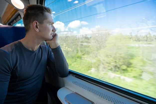 Młody mężczyzna siedzi w pociągu i wygląda przez okno.