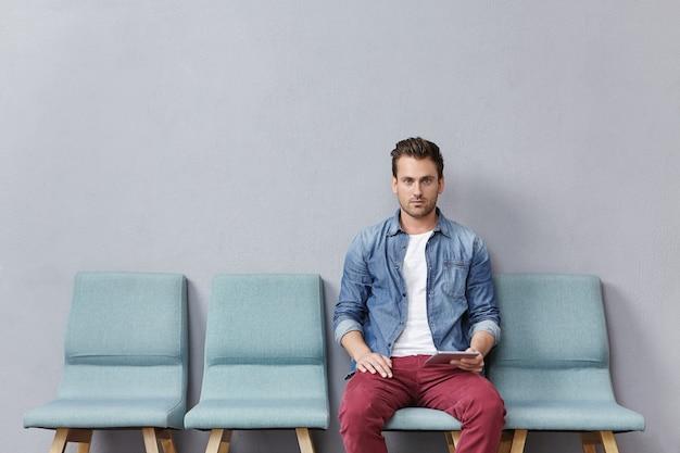 Młody mężczyzna siedzi w poczekalni trzymając tablet