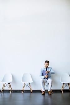 Młody mężczyzna siedzi w poczekalni z teczką w ręku i sprawdza czas przed rozmową kwalifikacyjną