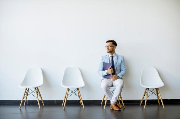 Młody mężczyzna siedzi w poczekalni z teczką w ręku przed rozmową kwalifikacyjną