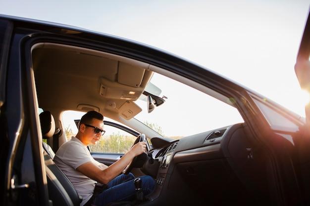Młody mężczyzna siedzi w samochodzie
