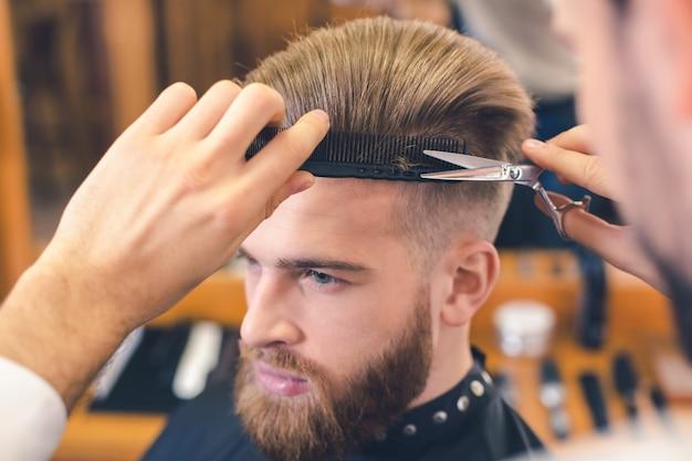 Młody mężczyzna siedzi w zakładzie fryzjerskim, podczas gdy fryzjer obcina włosy