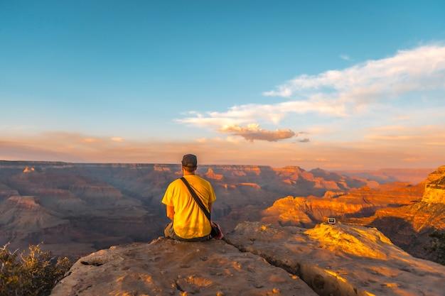 Młody mężczyzna siedzi w żółtej koszuli o zachodzie słońca w powell point w wielkim kanionie. arizona, zdjęcie pionowe