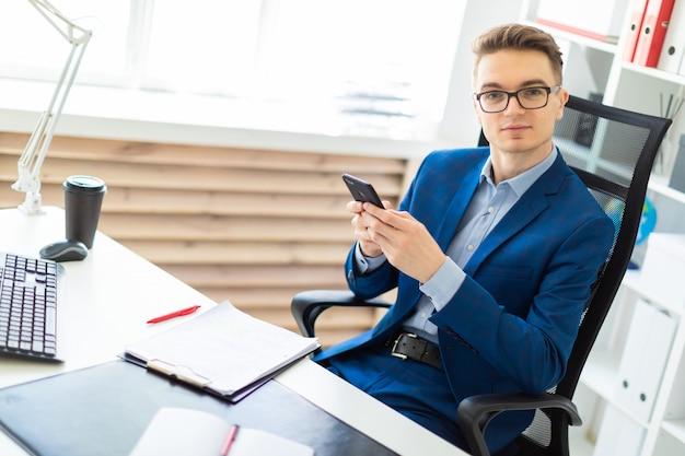 Młody mężczyzna siedzi z telefonem w rękach przy stole w biurze.