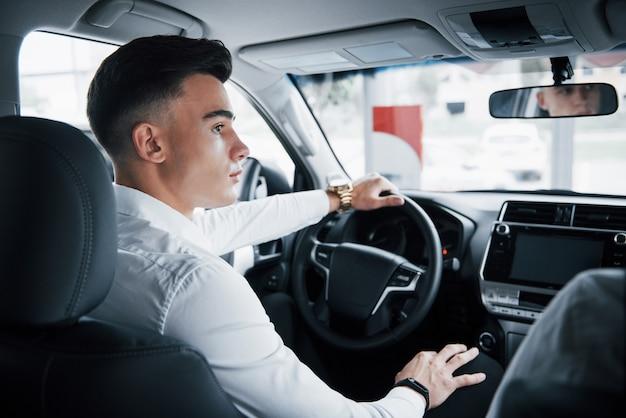 Młody mężczyzna siedzi za kierownicą w nowo zakupionym samochodzie, zakup udany.
