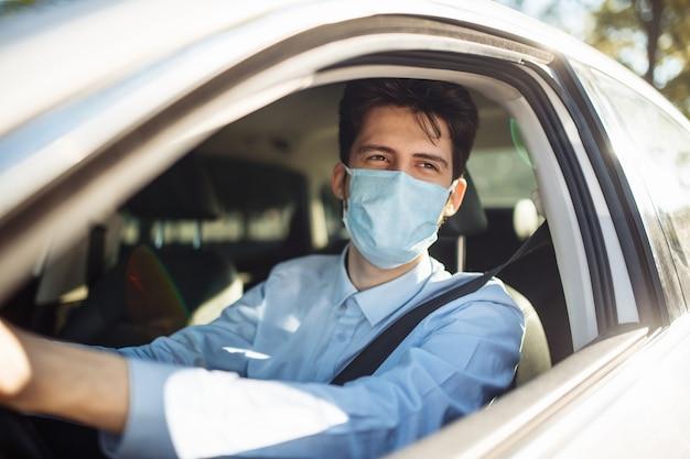 Młody mężczyzna siedzi za kierownicą w samochodzie ubrany w sterylną maskę medyczną. dystans społeczny, zapobieganie rozprzestrzenianiu się wirusa i koncepcja leczenia.