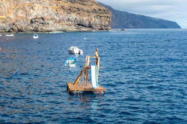 Młody mężczyzna skaczący do wody morskiej w zatoce puerto de puntagorda na wyspie la palma na wyspach kanaryjskich. hiszpania