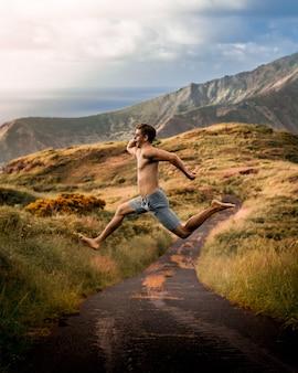 Młody mężczyzna skaczący na polu otoczonym górami w słońcu i pochmurnym niebie