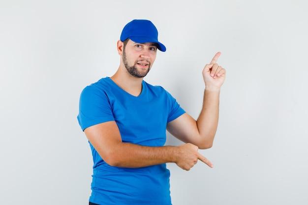 Młody mężczyzna skierowany w górę iw dół w niebieskiej koszulce i czapce i patrząc pozytywnie