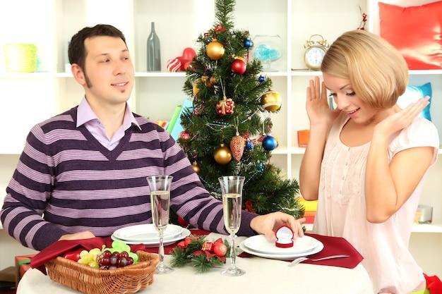 Młody mężczyzna składa propozycję, by poślubić dziewczynę przy stole w pobliżu choinki