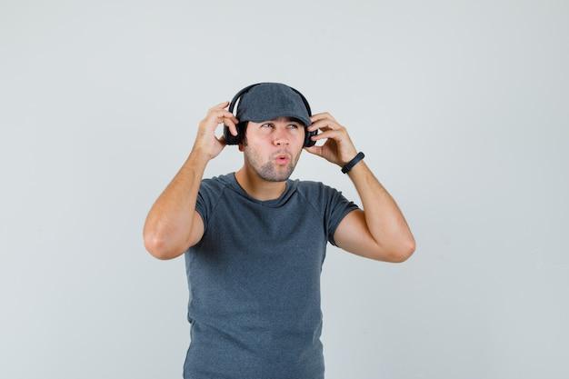 Młody mężczyzna słucha muzyki w słuchawkach w czapce t-shirt i wygląda zamyślony