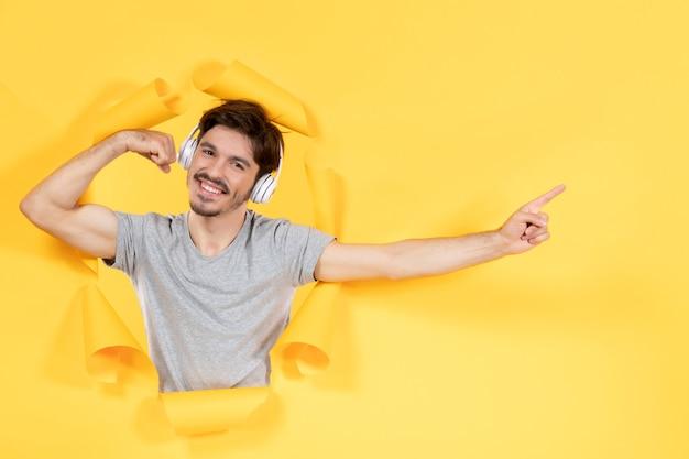 Młody mężczyzna słuchający muzyki w słuchawkach na żółtym papierze w tle brzmi dźwięk ultradźwiękowy