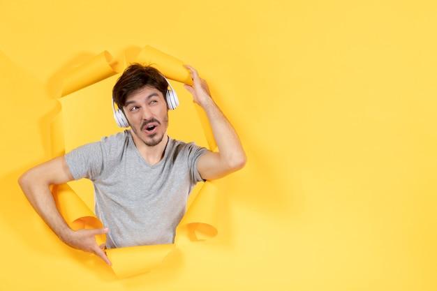 Młody mężczyzna słuchający muzyki w słuchawkach na żółtym papierze w tle dźwięki ultradźwiękowe