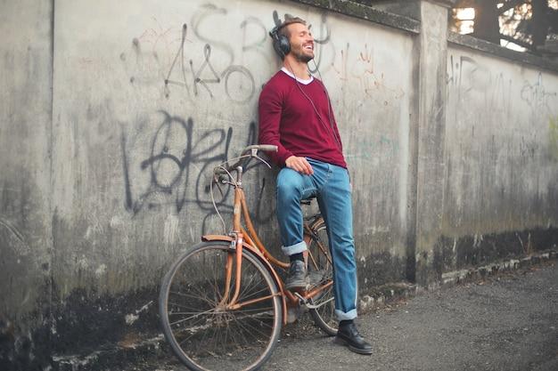 Młody mężczyzna, słuchanie muzyki i uśmiechnięty stojący przy ścianie na ulicy