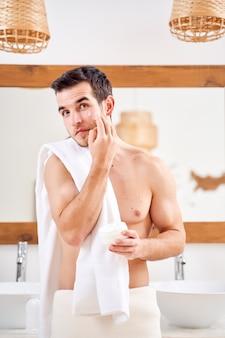 Młody mężczyzna smaruje twarz białym kremem, stojąc przed lustrem w wannie o poranku