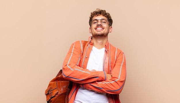 Młody mężczyzna śmiejący się radośnie ze skrzyżowanymi ramionami, o zrelaksowanej, pozytywnej i usatysfakcjonowanej pozie
