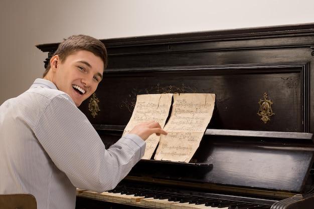 Młody mężczyzna śmieje się, gdy siedzi grając na pianinie