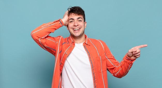 Młody mężczyzna śmieje się, wygląda na szczęśliwego, pozytywnego i zdziwionego, realizując świetny pomysł wskazujący na boczny