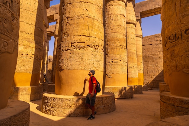 Młody mężczyzna spacerujący między kolumnami z hieroglifami wewnątrz świątyni karnak. egipt