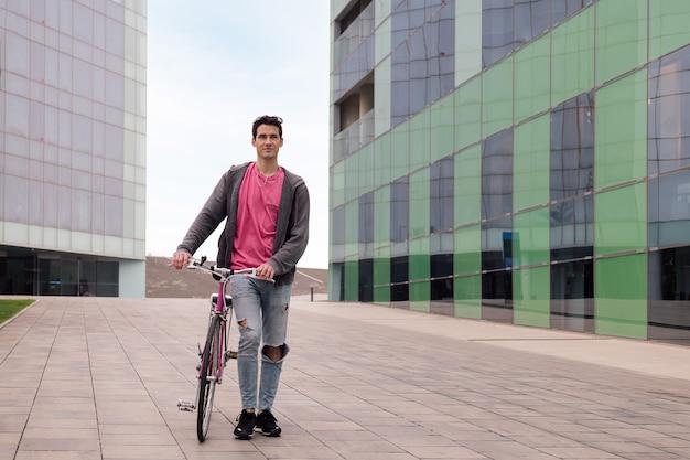 Młody mężczyzna spacerujący po mieście z koncepcją roweru retro zrównoważonego stylu życia
