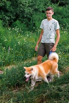 Młody mężczyzna spaceruje po letnim parku z młodym szczeniakiem rasy akita