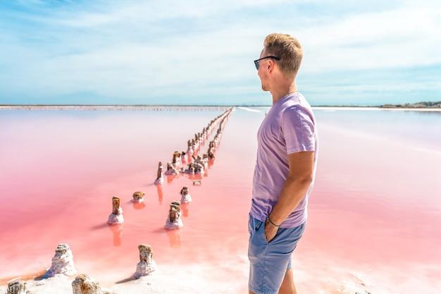 Młody mężczyzna spaceruje po słonym różowym jeziorze z błękitnym niebem spokojny krajobraz i relaks