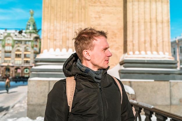 Młody mężczyzna spaceruje zimą po centrum petersburga obok katedry kazańskiej