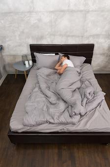 Młody mężczyzna śpi samotnie w stylowym łóżku w szarych kolorach i stoliku nocnym ze świecami w sypialni w stylu loft