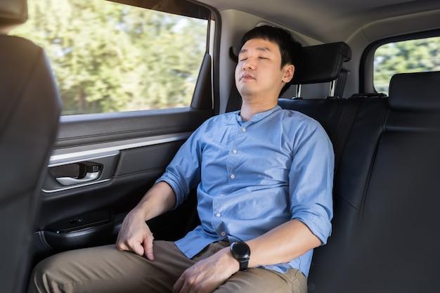 Młody mężczyzna śpi siedząc na tylnym siedzeniu samochodu