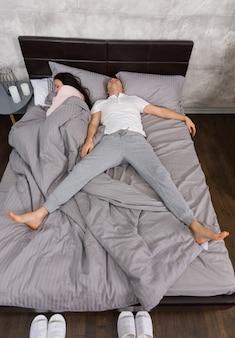 Młody mężczyzna śpiący w pozycji swobodnego spadania z żoną zajął całe łóżko, ubrany w piżamę, przy stoliku nocnym ze świecami