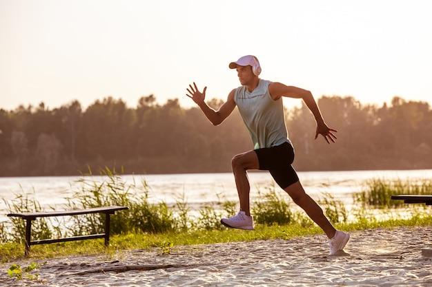 Młody mężczyzna sportowe ćwiczenia, słuchanie muzyki na zewnątrz nad rzeką