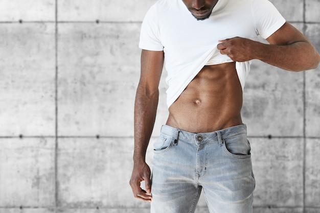 Młody mężczyzna sportowe na sobie stylowe dżinsy i białą koszulkę