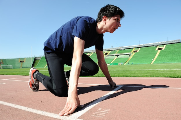 Młody mężczyzna sportowiec jest na początku bieżni na stadionie