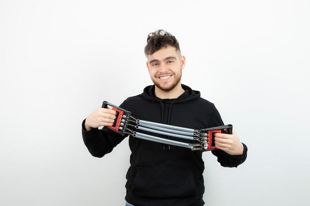 Młody mężczyzna sportowiec posiadający ćwiczenia na siłowni narzędzie na białej ścianie.