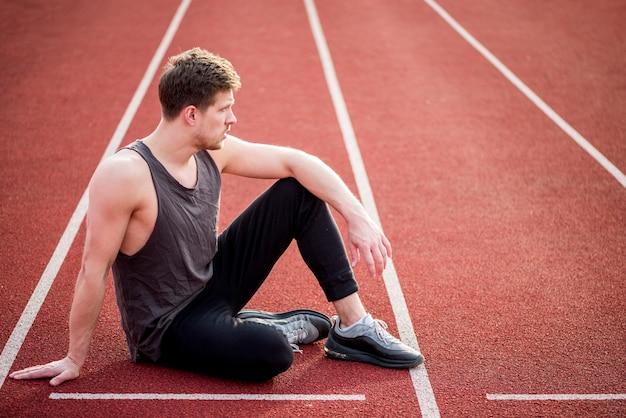 Młody mężczyzna sportowiec siedzi na linii startowej toru wyścigowego