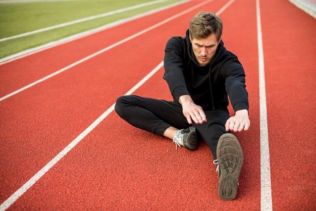 Młody mężczyzna sportowiec siedzi na torze wyścigowym, wyciągając rękę i nogi