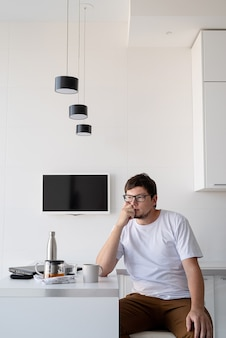 Młody mężczyzna spożywający śniadanie w domu, myślący