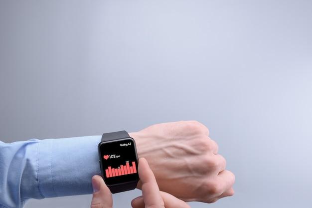 Młody mężczyzna sprawdza i monitoruje tętno za pomocą aplikacji w inteligentnym zegarku