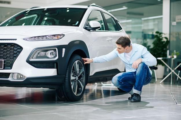 Młody mężczyzna sprawdza opony nowego samochodu w salonie