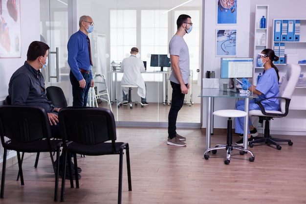 Młody mężczyzna sprawdzający spotkanie z poszanowaniem dystansu społecznego w szpitalnej poczekalni, pielęgniarka patrząca w komputer w masce przeciw covid-19