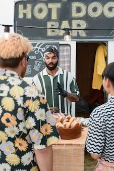 Młody mężczyzna sprzedający fast foody ludziom na zewnątrz na plaży?