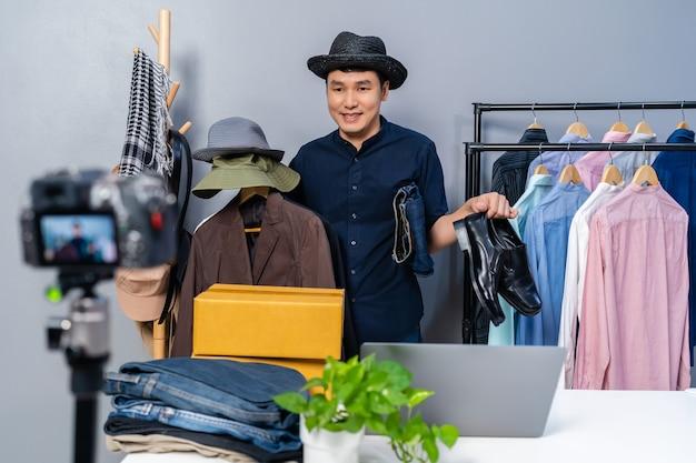 Młody mężczyzna sprzedający ubrania i akcesoria online za pomocą transmisji na żywo z kamery. biznesowy handel elektroniczny w domu